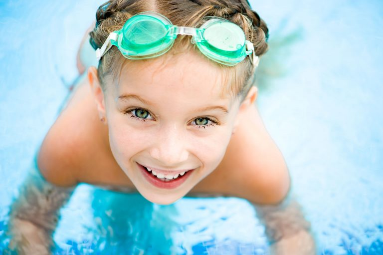 child with green goggles swimming
