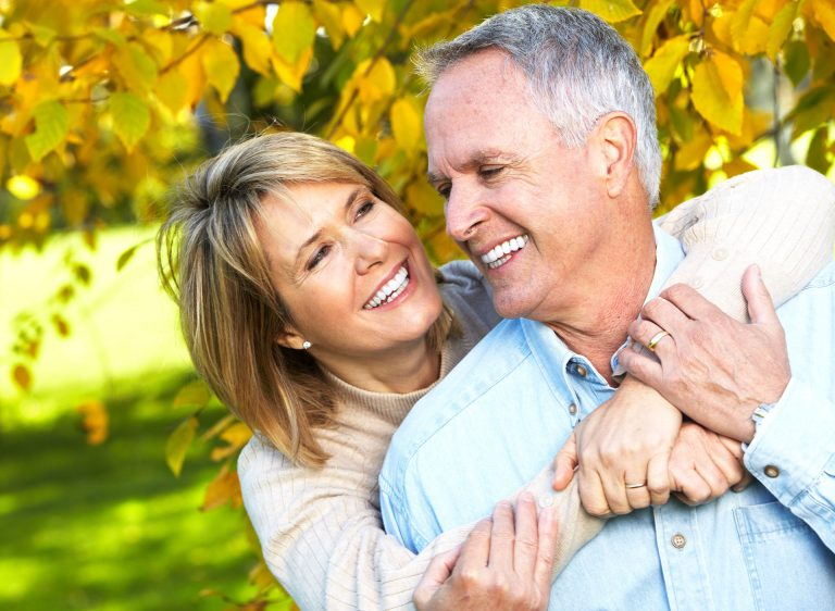 old couple hugging and smiling under tree