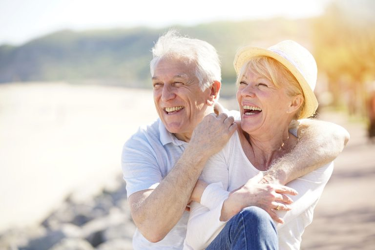 old couple smiling looking to the left sunny weather