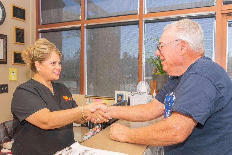 Orangecrest Dental staff member and patient shaking hands